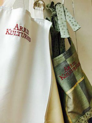 """Bilden visar två förkläden som det står """"Arrie kulturhus"""" på."""
