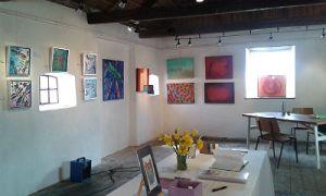 Bilden visar ett rum med vita väggar där tavlor hänger.